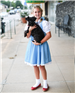 Girl dressed up as Dorothy from the Wizard of Oz and holding Toto