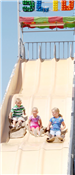 3 kids riding down a large slide