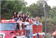 High school kids on top of a fire truck during a parade
