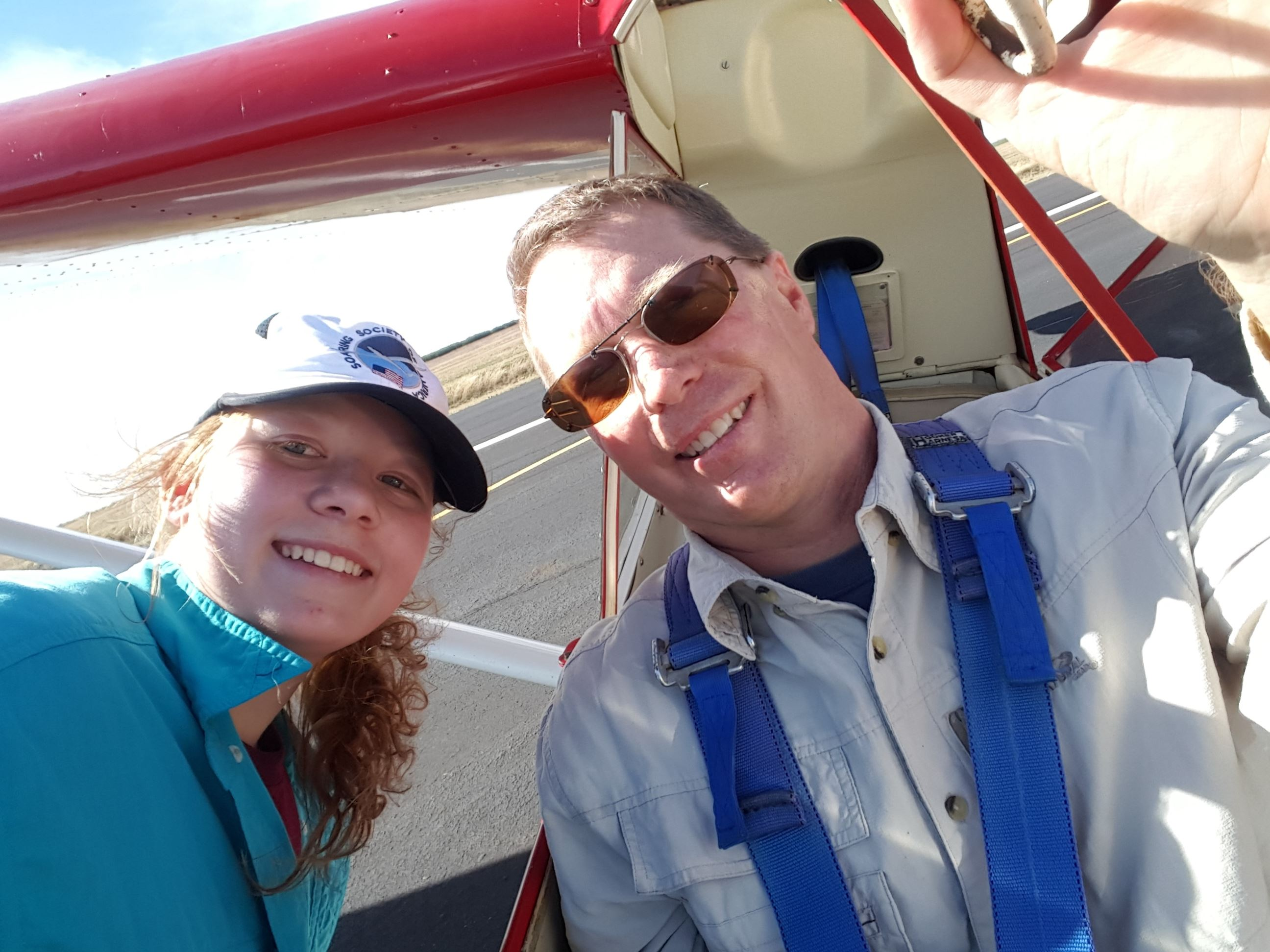 Selfie of man inside a glider with girl standing outside